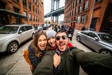 Happy Friends Tourist Taking Selfie In Manhattan Bridge Seen From Dumbo, Brooklyn, New York City, USA