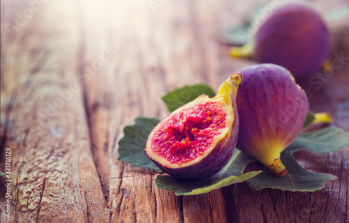 Obraz Ripe fig fruits with leaf close-up. Beautiful sweet fresh organic figs on a wooden table. Border label design. Healthy vegan food - fototapety do salonu