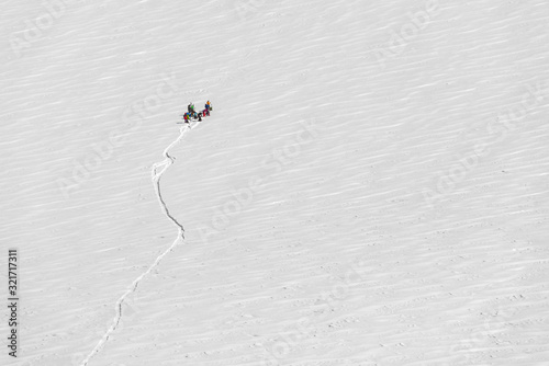 Group of hikers and skiers on a huge giant snowfield up in the mountains with a Tapéta, Fotótapéta