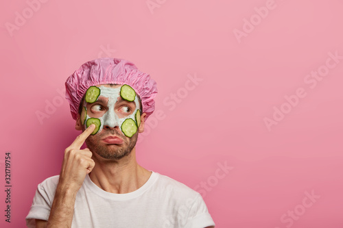 Puzzled man points at face, looks aside, claims on having blackheads, applies cucumbers and clay mask, wears bath cap, purses lower lip, isolated over pink wall, copy space aside Canvas Print