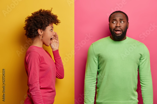 Photo Emotive young curly woman stands in profile and screams loudly at guilty man who