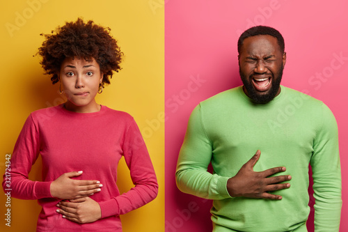 Cuadros en Lienzo Horizontal shot of dark skinned couple touch stomachs, suffer from chronic gastritis, being hungry has displeased face expressions, isolated over yellow and pink background