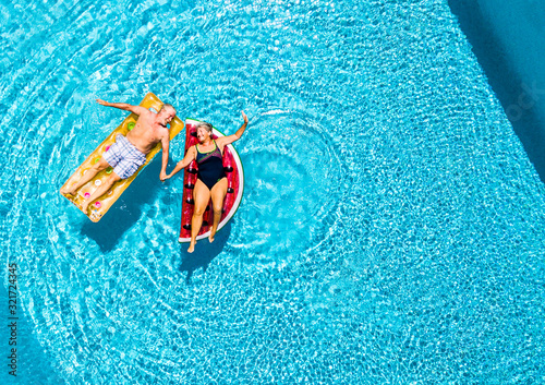 Fototapeta Vertical view of happy couple of old senior people enjoying the summer holiday vacation at the blue water pool with coloured treny lilos together with fun and love obraz