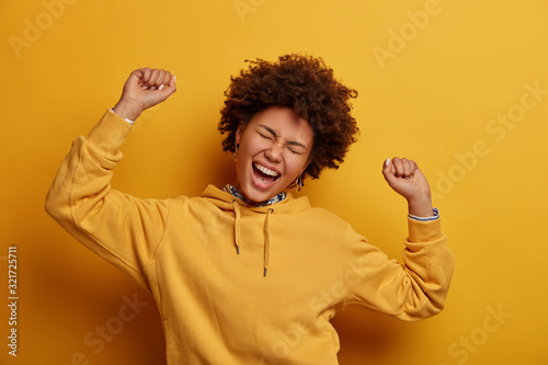 Fototapeta Relaxed lazy upbeat woman keeps arms raised up in air, enjoys weekends, dances joyfully on disco party, closes eyes and squints face, wears hoodie, feels alive, poses over vibrant yellow background obraz