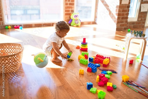 Obraz Adorable toddler playing with building blocks around lots of toys at kindergarten - fototapety do salonu