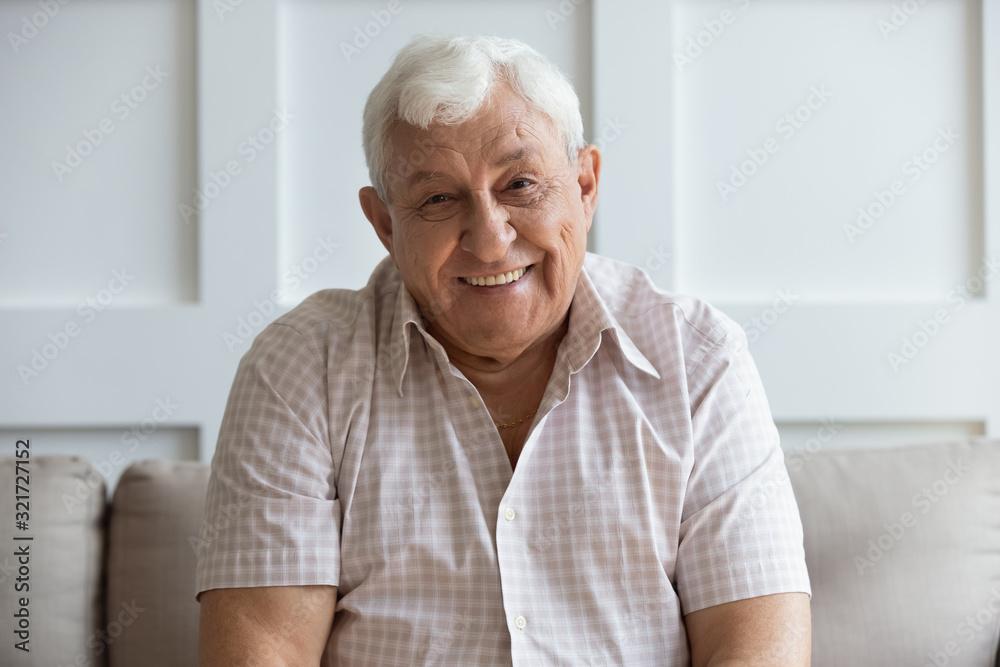 Fototapeta Headshot portrait of smiling mature man relaxing on sofa