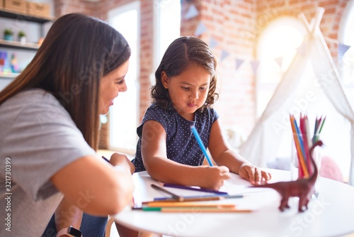 Foto Beautiful teacher and toddler girl drawing draw using colored pencils at kinderg