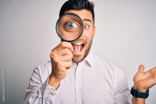 Obraz na plátně Young detective man looking through magnifying glass over isolated background ve