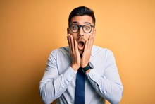 Young Handsome Businessman Wearing Tie And Glasses Standing Over Yellow Background Afraid And Shocked, Surprise And Amazed Expression With Hands On Face