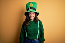 Beautiful Curly Hair Woman Wearing Green Hat With Clover Celebrating Saint Patricks Day With A Happy And Cool Smile On Face. Lucky Person.