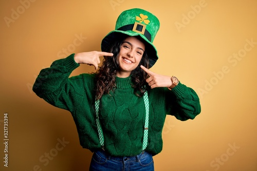 Beautiful curly hair woman wearing green hat with clover celebrating saint patricks day smiling cheerful showing and pointing with fingers teeth and mouth Fototapeta