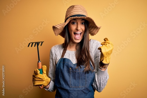 Young beautiful farmer woman wearing apron and hat using rake over yellow backgr Wallpaper Mural