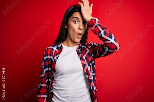 Foto Young beautiful brunette woman wearing casual shirt standing over isolated red background surprised with hand on head for mistake, remember error