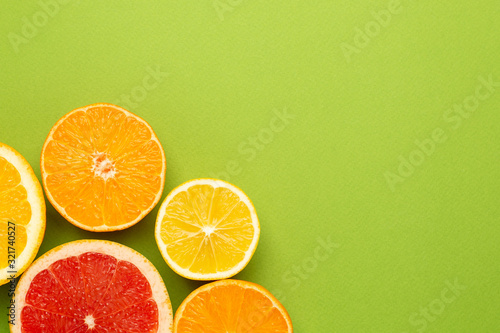 Citruses fruits on green background with copyspace, fruit flatlay, summer minimal compositon with grapefruit, lemon, mandarin and orange