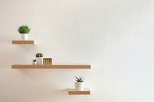 Wooden Shelves With Beautiful Plants And Calendar On Light Wall