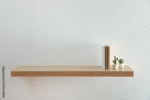 Photo Wooden shelf with books and decorative cactuses on light wall