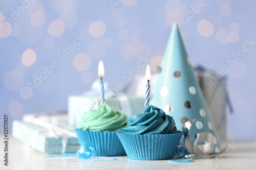 Delicious birthday cupcakes with cream and burning candles on white table Wallpaper Mural
