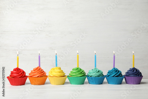 Photo Delicious birthday cupcakes with burning candles on white wooden table