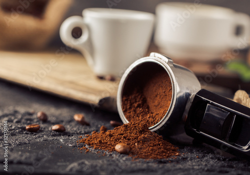 Fototapeta Ground coffee and coffee beans on old cafe table. obraz