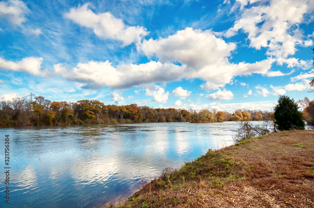 Fototapeta A wide angle shot of the Catawba river in South Carolina with a blue sky and white fluffy clouds.