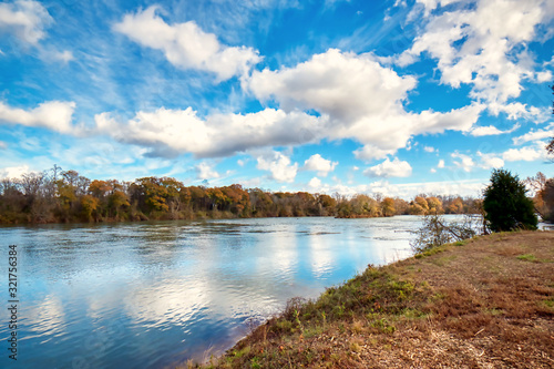 A wide angle shot of the Catawba river in South Carolina with a blue sky and white fluffy clouds Fotobehang