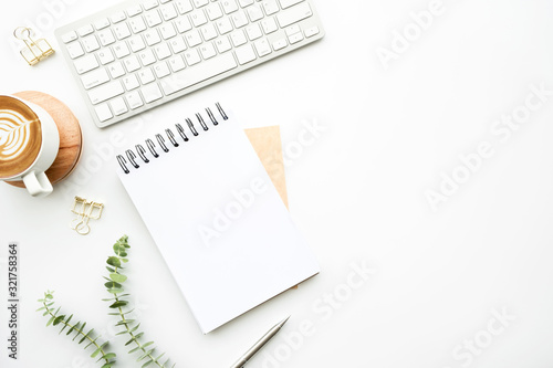 Obraz Blank notebook is on top of white minimal office desk table with cup of latte coffee and supplies. Top view with copy space, flat lay. - fototapety do salonu