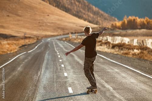 Cuadros en Lienzo Lonely skateboarder on longboard at mountain road