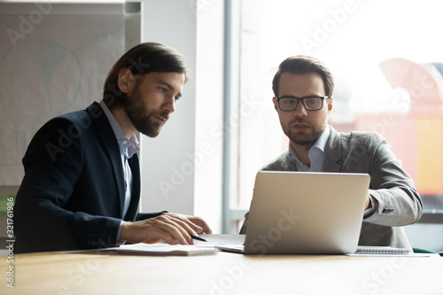 Fototapety, obrazy: Two serious businessmen colleagues discussing project, looking at laptop screen