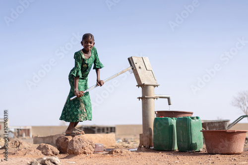 Fototapeta Happy Aboriginal Young Girl with lots of Water in a village