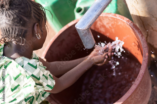 Photo Cute African Ethnicity Offspring Transporting nutritious Water for an insufficie