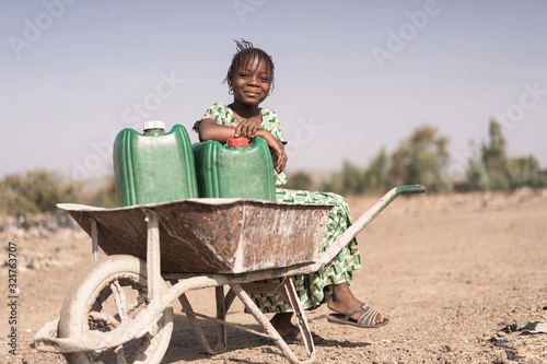 Joyful African Young Woman Transporting Natural Water for lack of water symbol Wallpaper Mural