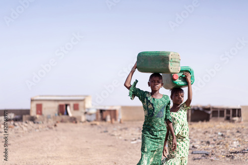 Fototapeta Working African Ethnicity Schoolgirl Collecting Fresh Water for lack of water sy