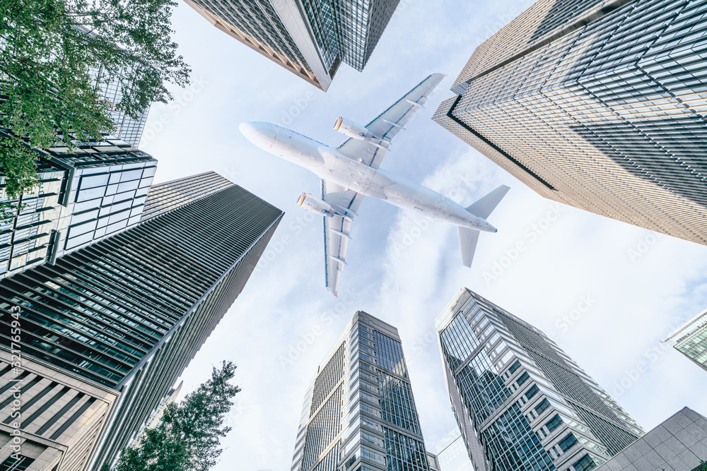 Fototapeta Aircraft flying above glass office buildings in the sky over city buildings in financial district of Tokyo city, Japan
