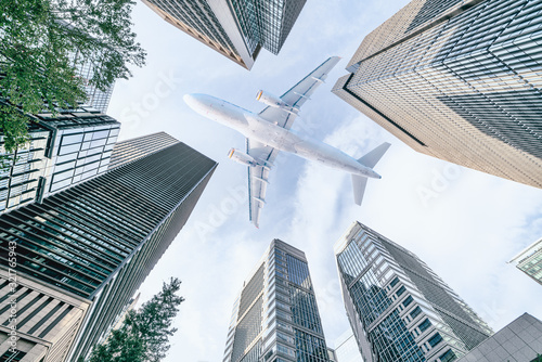 Fototapeta Aircraft flying above glass office buildings in the sky over city buildings in financial district of Tokyo city, Japan obraz