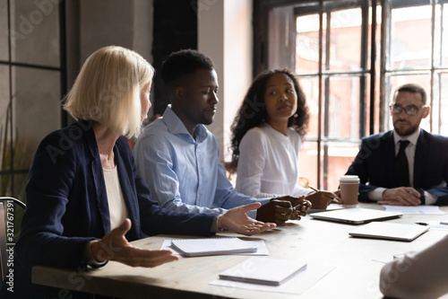 Fototapety, obrazy: Diverse team listening aged leader during group meeting in boardroom