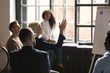 Aged curious woman raised hand ask question at corporate seminar