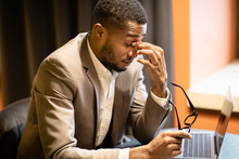 Exhausted Black Manager Massaging Nose And Using Laptop