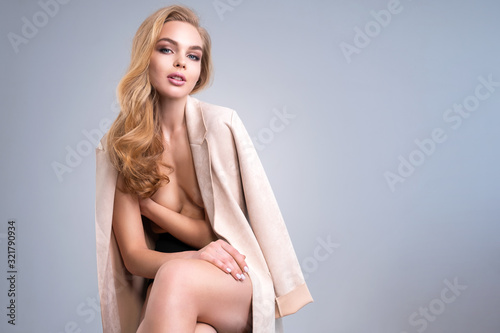 Sexy Fashion model in beige jacket hiding bare breasts. Sensual girl dressed jacket on a nude body. Beautiful young woman posing at studio.  Blonde long brown hair and natural makeup.