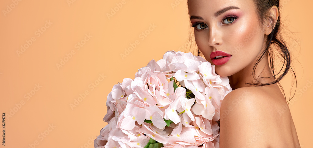 Fototapeta Beautiful white girl with flowers. Stunning brunette girl with big bouquet  of hydrangeas. Closeup face of young beautiful woman with a healthy clean skin. Pretty woman with bright makeup