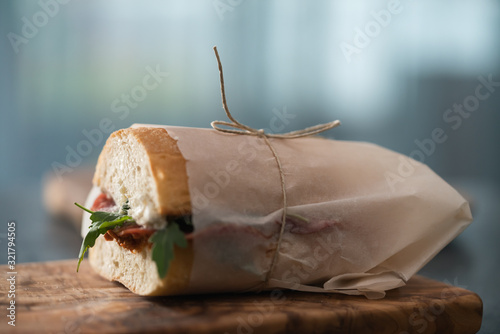 Cuadros en Lienzo Ciabatta sandwich with salame, arugula, red pesto and cream cheese wrapped in pa