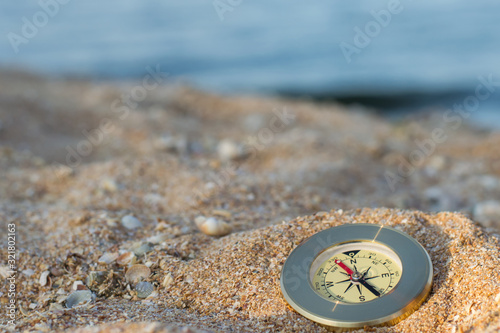 A compass showing the direction lies on the sea sand with shells Canvas Print