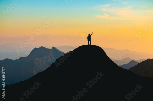 Fototapeta The silhouette of a man with a cheerful raise in his hand on the top of the mountain During sunset time The concept of effort and success obraz