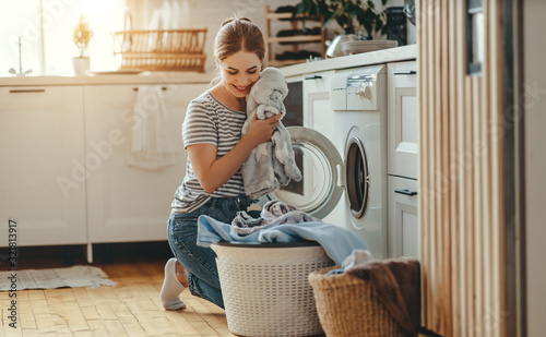 Obraz Happy housewife woman in laundry room with washing machine  . - fototapety do salonu