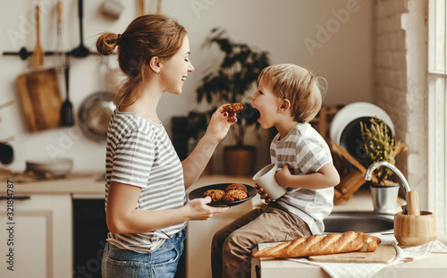 Obraz preparation of family breakfast. mother and child son cut bread  and eat cookies with milk in morning - fototapety do salonu
