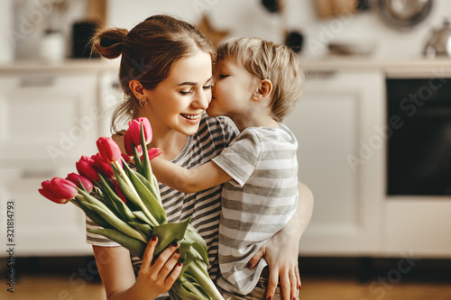 Fototapeta happy mother's day! child son gives flowers for  mother on holiday obraz