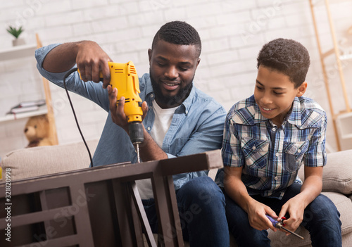 Obraz Black father teaching his son how to use drill perforator - fototapety do salonu