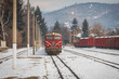 Velingrad railway station, Bulgaria - February 8, 2020: Train with red locomotive and green wagons arrives at the train station.