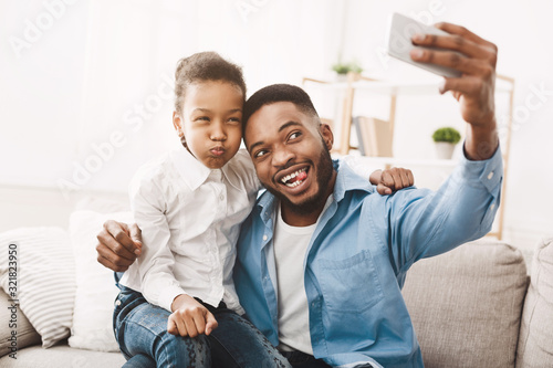 Happy afro father taking selfie with his funny daughter Wallpaper Mural