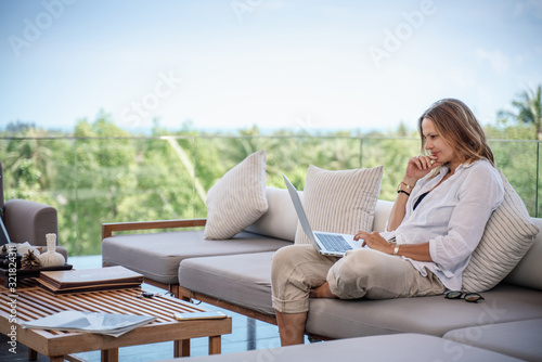Attractive woman 40 years old in a white shirt sitting on a gray sofa working on Canvas Print