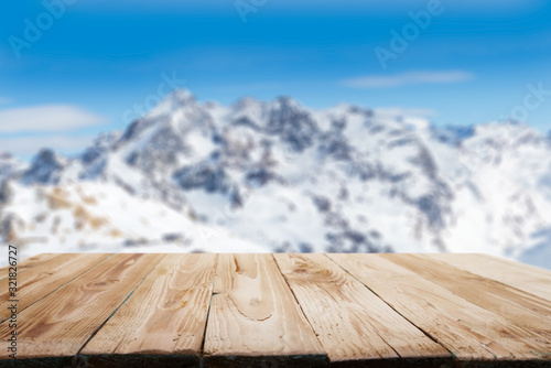 Fototapeta Empty wooden surface against snowy mountainous area on winter day. obraz